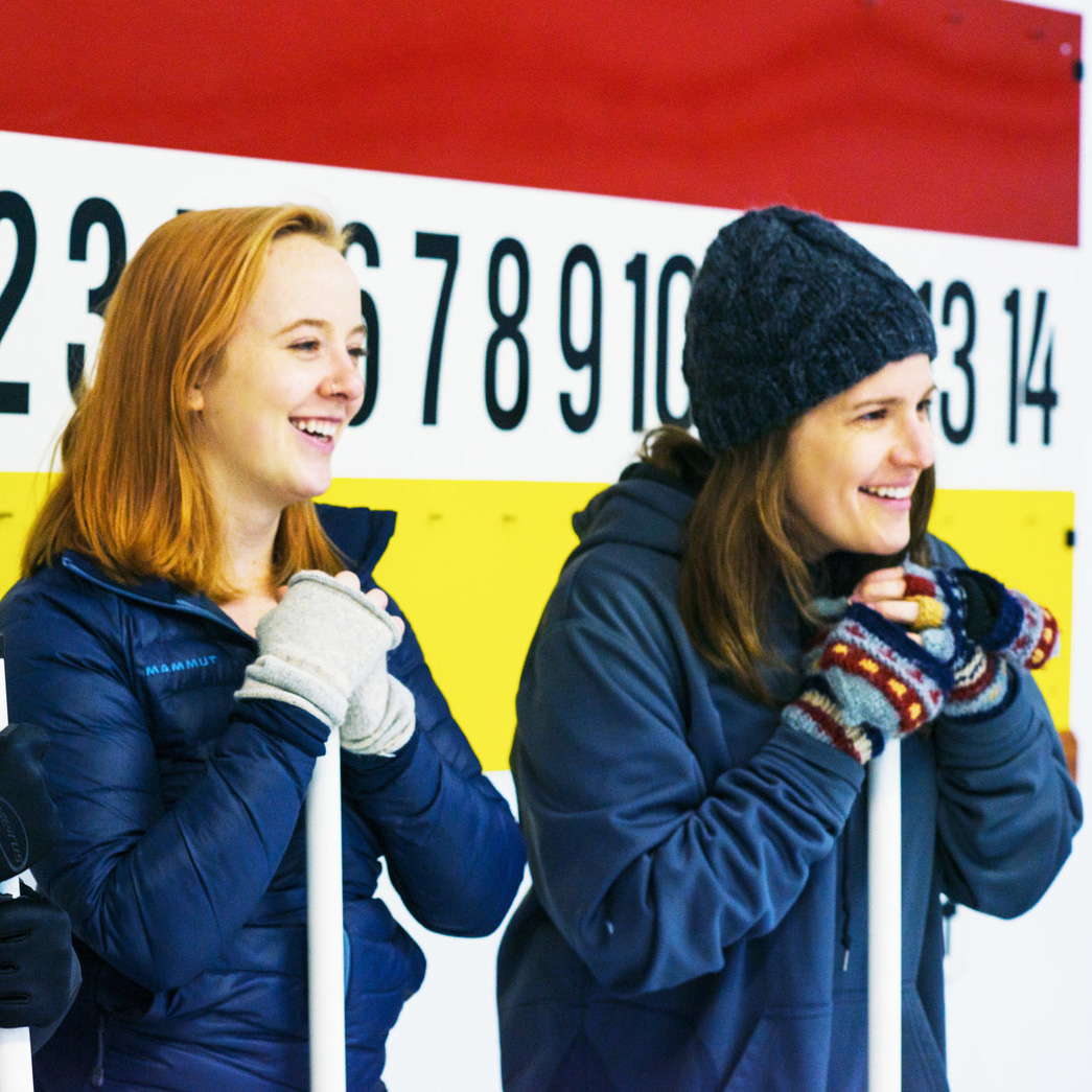 two women standing with curling brooms